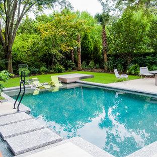 Diseño de piscina con fuente natural, actual, grande, rectangular, en patio trasero, con adoquines de hormigón