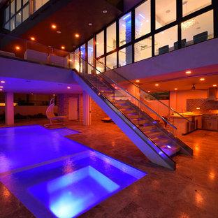 Ejemplo de piscina contemporánea, grande, rectangular, en patio trasero, con adoquines de piedra natural