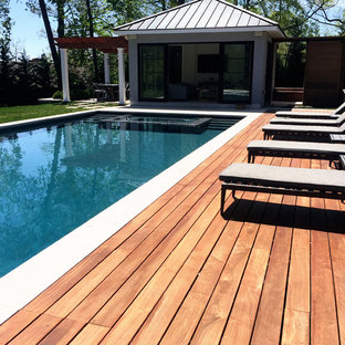 Photo of a mid-sized contemporary backyard rectangular lap pool in New York with a pool house and decking.
