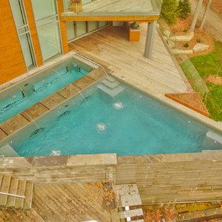 Ejemplo de piscina con fuente infinita, contemporánea, grande, a medida, en patio trasero, con entablado