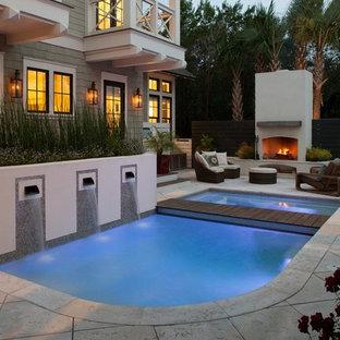 Cette photo montre une piscine naturelle et arrière chic de taille moyenne et sur mesure avec un bain bouillonnant et des pavés en béton.