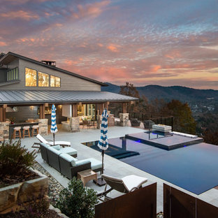 Trendy tile and rectangular infinity hot tub photo in Other