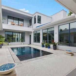 Aménagement d'une piscine à débordement contemporaine de taille moyenne et rectangle avec une cour et du béton estampé.
