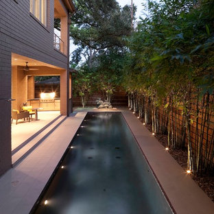 Photo of a mid-sized contemporary side yard rectangular pool in Houston with tile.
