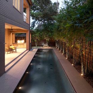 Inspiration för en mellanstor funkis rektangulär pool längs med huset, med kakelplattor