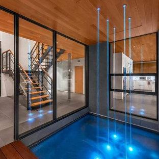 Foto de piscina con fuente alargada, contemporánea, de tamaño medio, rectangular, en patio trasero, con entablado