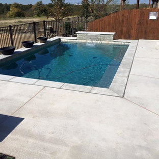 Diseño de piscina con fuente alargada, actual, pequeña, rectangular, en patio trasero, con losas de hormigón