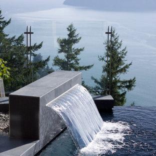 Ejemplo de piscina con fuente infinita, actual, a medida, en patio trasero