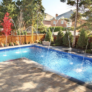 Inspiration for a large contemporary backyard concrete paver and l-shaped lap pool remodel in Toronto
