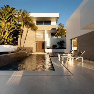 Foto de casa de la piscina y piscina elevada, actual, de tamaño medio, rectangular, en patio lateral, con suelo de baldosas