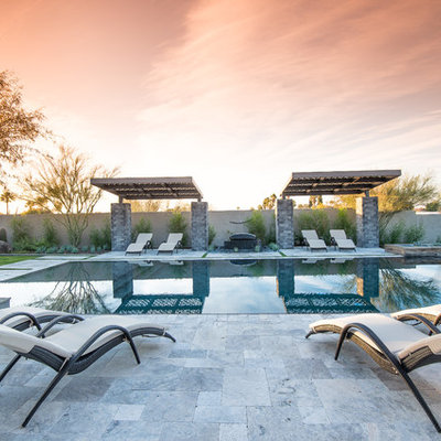 Inspiration for a large contemporary backyard stamped concrete and rectangular infinity pool remodel in Phoenix