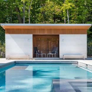 Foto de casa de la piscina y piscina actual, pequeña, rectangular, en patio trasero, con adoquines de hormigón