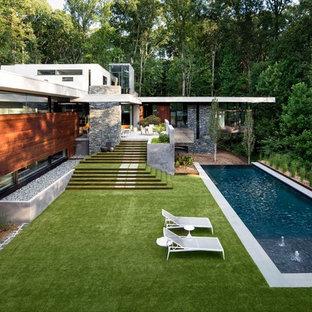 Ejemplo de piscina con fuente alargada, actual, extra grande, rectangular, en patio trasero