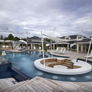 Cette photo montre une très grand piscine arrière et à débordement tendance sur mesure avec du carrelage.