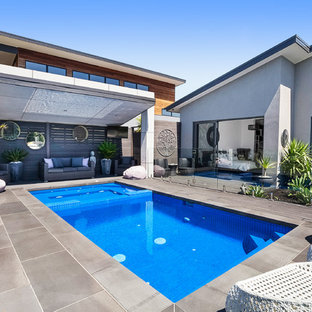 Contemporary backyard rectangular lap pool in Melbourne with a hot tub.