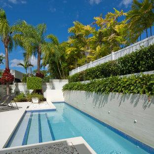 Imagen de piscina alargada, actual, de tamaño medio, a medida, en patio trasero, con suelo de baldosas