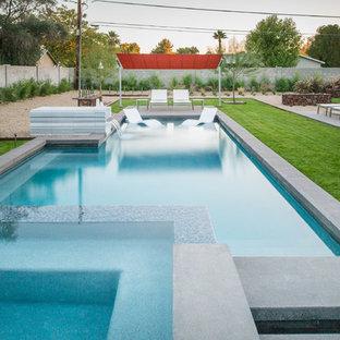 Foto de piscinas y jacuzzis alargados, actuales, grandes, rectangulares, en patio trasero, con losas de hormigón