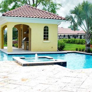 Imagen de casa de la piscina y piscina alargada, contemporánea, grande, a medida, en patio trasero, con suelo de hormigón estampado