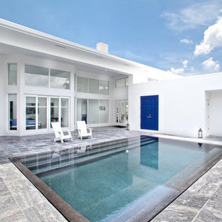 Example of a mid-sized minimalist backyard tile and rectangular lap pool design in Miami