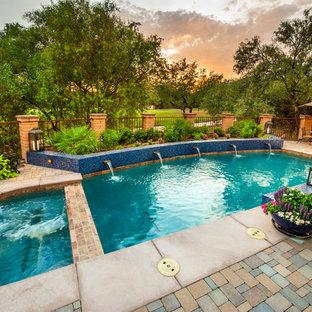 Foto de piscinas y jacuzzis actuales, de tamaño medio, a medida, en patio trasero, con adoquines de ladrillo