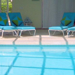 Ejemplo de casa de la piscina y piscina alargada, tropical, grande, interior y rectangular, con suelo de hormigón estampado