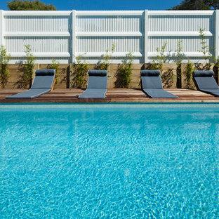 Diseño de piscina natural, costera, rectangular, en patio delantero, con entablado