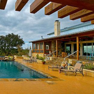 Foto di una grande piscina monocorsia moderna rettangolare dietro casa con una vasca idromassaggio e cemento stampato