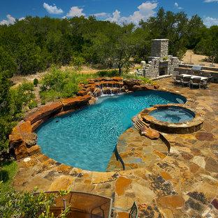 Ejemplo de piscina con fuente rústica, de tamaño medio, en patio trasero, con adoquines de piedra natural