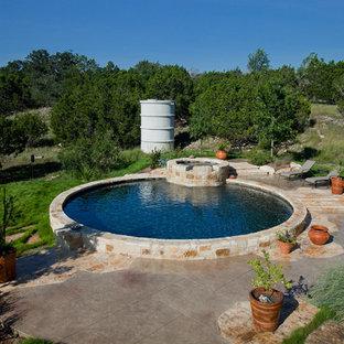 Diseño de piscina con fuente elevada, rural, de tamaño medio, redondeada, en patio trasero, con suelo de hormigón estampado