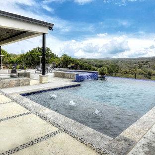 Imagen de piscina infinita, grande, rectangular, en patio trasero, con privacidad y losas de hormigón