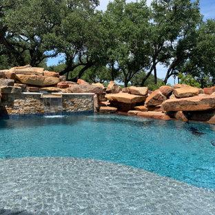 Immagine di un'ampia piscina naturale rustica personalizzata dietro casa con pedane