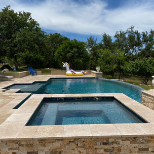 Photo of an expansive modern backyard custom-shaped infinity pool in Austin with with privacy feature and decking.