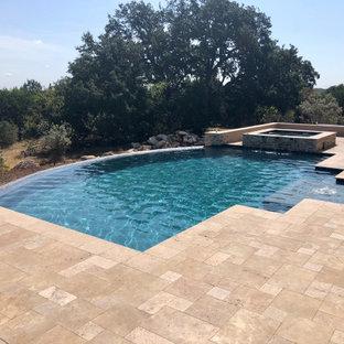 Ejemplo de piscina infinita, moderna, extra grande, a medida, en patio trasero, con privacidad y entablado