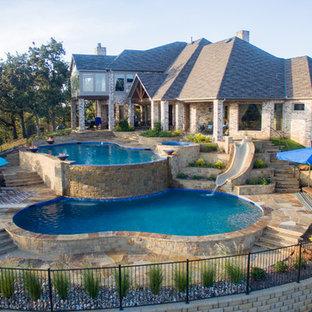 Foto de piscina con tobogán infinita, clásica renovada, grande, a medida, en patio trasero, con adoquines de piedra natural
