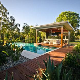 Ispirazione per una grande piscina a sfioro infinito contemporanea personalizzata nel cortile laterale con una vasca idromassaggio e pedane