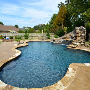 Design ideas for a medium sized rustic back custom shaped lengths swimming pool in Little Rock with a water slide and natural stone paving.