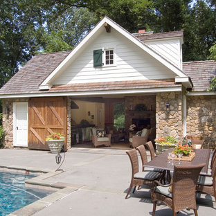 Traditional swimming pool in Philadelphia with concrete slabs and a pool house.