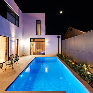 Photo of a mid-sized contemporary courtyard rectangular lap pool in Melbourne with concrete pavers.
