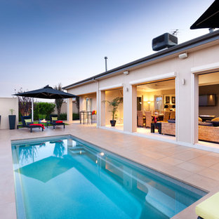 Contemporary courtyard rectangular lap pool in Other with tile.