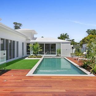 Ejemplo de piscina alargada, contemporánea, rectangular, en patio trasero, con entablado