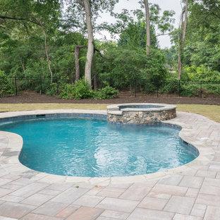Foto de piscinas y jacuzzis alargados, de estilo americano, de tamaño medio, tipo riñón, en patio trasero, con suelo de baldosas