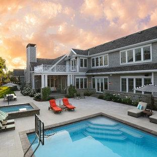 Ejemplo de piscina de estilo americano, grande, rectangular, en patio trasero, con suelo de baldosas