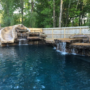 This is an example of a large country backyard custom-shaped lap pool in Houston with a water slide and natural stone pavers.
