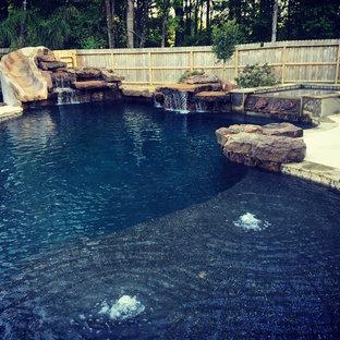Foto di una grande piscina monocorsia stile americano personalizzata dietro casa con un acquascivolo e pavimentazioni in pietra naturale
