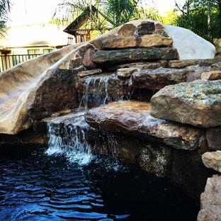 Diseño de piscina con tobogán alargada, de estilo americano, de tamaño medio, redondeada, en patio trasero, con adoquines de piedra natural