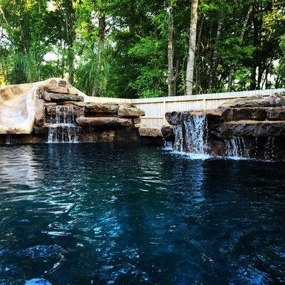 Mid-sized mountain style backyard stone and custom-shaped lap water slide photo in Houston