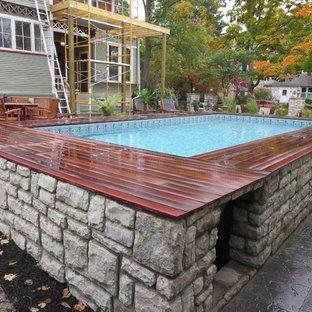 Foto de piscina elevada, clásica renovada, de tamaño medio, rectangular, en patio trasero, con adoquines de hormigón