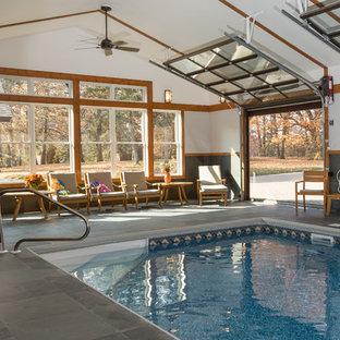 Ejemplo de casa de la piscina y piscina rústica, grande, rectangular y interior, con suelo de baldosas