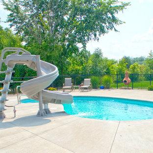 Modelo de piscina con tobogán minimalista, de tamaño medio, tipo riñón, en patio trasero, con losas de hormigón