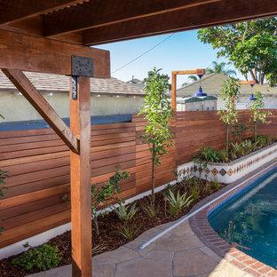 Diseño de piscina alargada, clásica, de tamaño medio, tipo riñón, en patio trasero, con adoquines de piedra natural